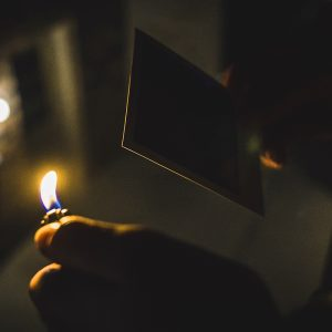 holding a burning match next to photograph