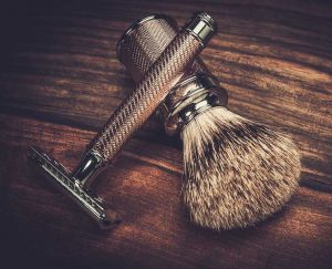 Matching set of safety razor and shaving brush on wood counter