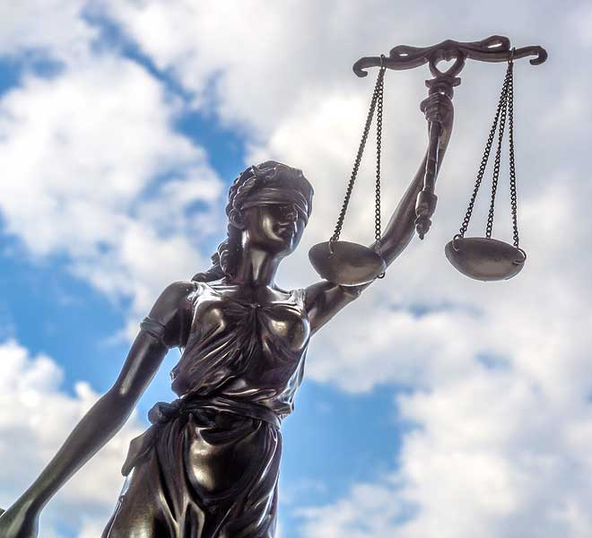 metal statue of Justice as a woman wearing a blindfold and holding up a set of evenly balanced scales